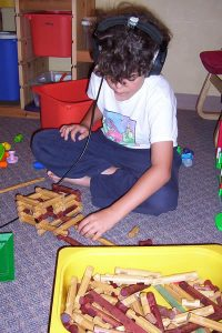 boy listening to head phones playing with a puzzle